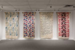 Image shows 4 pieces of printed textiles in an exhibition