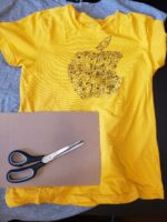 A yellow t-shirt, a rectangular piece of cardboard and a pair of scissors are laid on a table