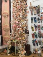 Image shows a wall. Hanging on the left of the image is an artwork – a banner hangs vertically. The banner is pink-flesh coloured and has applique eyelid textile sculptures along the length. In the centre are dozens upon dozens of textile flower strings. They vary in colour from pinks to oranges to whites. On the right on the image are plastic organizational pouches containing the tools of an artist: paintbrushes, scissors, string and various other tools.