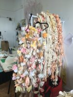A large pile of textile sculpted flowers. The flowers are various pastel warm tones, ranging from whites, to pink, yellow and orange.