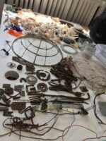Image shows a white tabletop covered in pieces of scrap metal of various sizes.