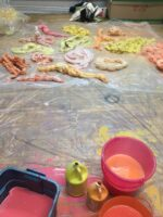 An image of Tau Lewis' process – in the foreground on the image are buckets of paint resting on a plastic sheet on the floor. In the background are textile pieces, likely dipped into the paints, coiled, and left to dry.