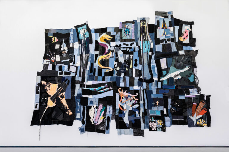 """Image shows Tau Lewis' piece """"The coral reef preservation society"""". A large, uneven quilt made from dark fabrics. Across the fabric are applique sea creatures, created from various swathes of colourful fabric. There is a sea horse, jellyfish, a sting ray, a turtle, a hammerhead shark, coral, and other small fish."""