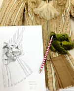 A sketchpad, pencil and part of a costume